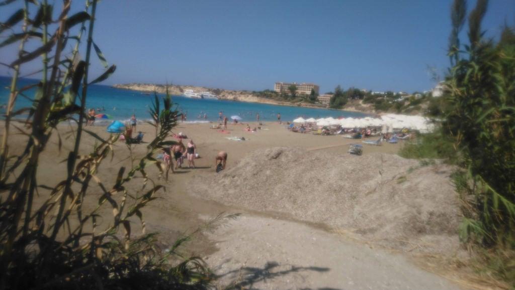 Bild av Coral bay. mesesettembre spiaggia gente mare sea oceano mediterraneo acqua cipro ombrelloni natura