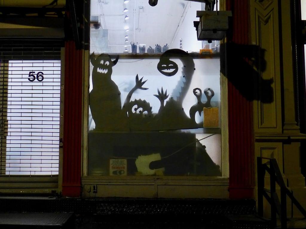 Attēls no TriBeCa. storefront monsters cutout shadows tribeca nyc